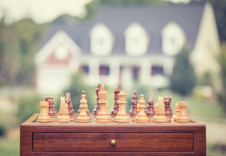 36468114 - real estate sale, home savings, loans market concept. housing industry mortgage plan and residential tax saving strategy. chess game figures isolated outside home background. focus on desk. homeowner